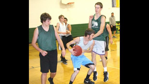 Cobra Lane Holliday (shown above, middle) corrals a rebound between teammates Braden Dohl (left) and Brady Holliday (right) at a recent practice. All three of those players, among several others, are fighting for playing time early on this season as part of a very competitive team, according to coach Chris Brown.