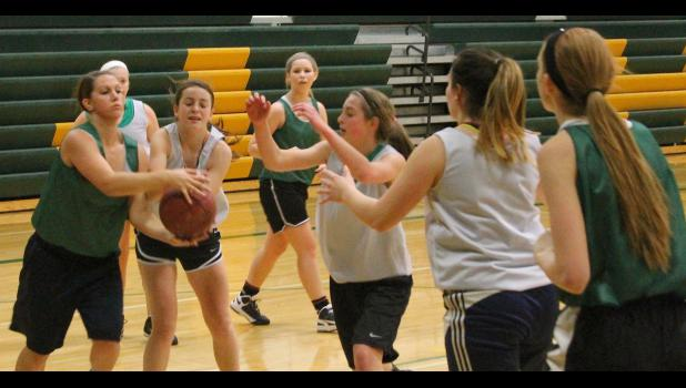 Cobra Brianna Cattrell (shown above, far left) fights for a rebound with Shelby Zule while teammate Kate Lierz (middle) also looks to get into the mix at recent practice.