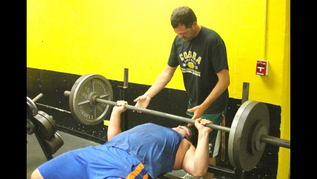 JHHS coach Caleb Wick (shown above, standing) spots Wyatt Roles as he works on the bench press during a weight room session earlier this summer.