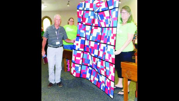Bob Lamberson (left) was one of 49 area veterans who were honored during the Quilts of Valor event here Saturday. Presenting the quilt to Lamberson was Connie Morgan (right) and Sandi Butler (background).