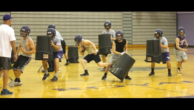 Panther running back Garrett Schultz (shown above, middle) works his way up the gym floor while his teammates run through their blocking schemes during Royal Valley's recent camp.