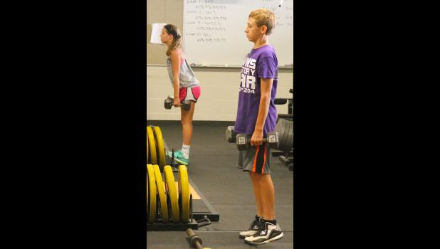 RV athletes Alyssa Gooderl (back left) and Garrett Pruyser (right) work with some free weights in the RVHS weight room over the summer.