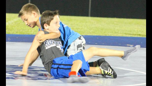 "Kit Jackson (shown above, back right) tries to maintain control of his opponent, Jack Brown (front left), in order to pin him to the mat. Jackson and Brown were matched up in the ""Showdown at Sundown"" dual, which HHS coach Cullen Jackson said is a fun way to wrap up the Wildcats' wrestling camp and send the athletes out on a positive note."