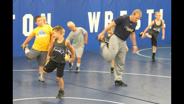 Wayland Baptist University coach and HHS alum Aaron Meister (shown above, middle) leads some of the younger Wildcats through stretches before starting the youth session of Holton's camp last Wednesday. Meister said he is glad to help the program when he can, passing on his knowledge to the next generation of Wildcat wrestlers.