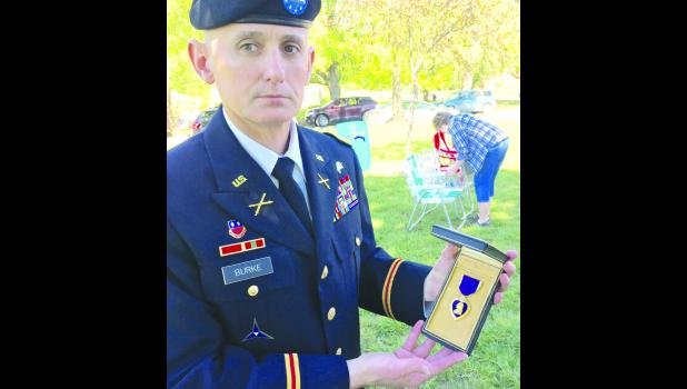 The photo shows Col. Thomas Burke, keynote speaker for the event, holdng a Purple Heart Medal that had been awarded to his uncle, he said.