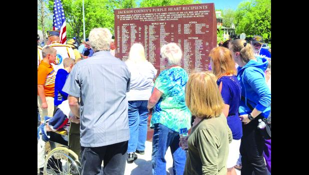 The photo here shows people reading the names of the soldiers etched into the backside of the monument, after it was unveiled here Saturday.