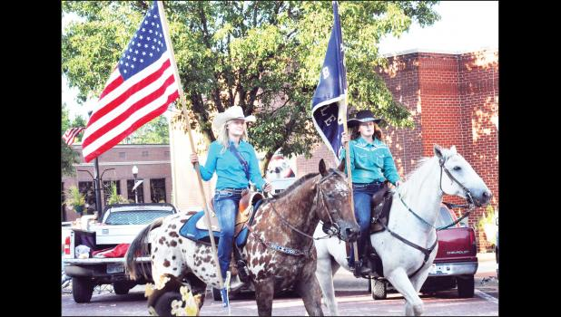 The recent Jackson County Fair Parade drew a variety of entries last week, including Circleville Saddle Club members MaKenna Jacobson (left) and Alex Rollins carrying the American flag and their club flag through the parade route. Check out Monday's Recorder for the annual fair section. (Photo by Ali Holcomb)