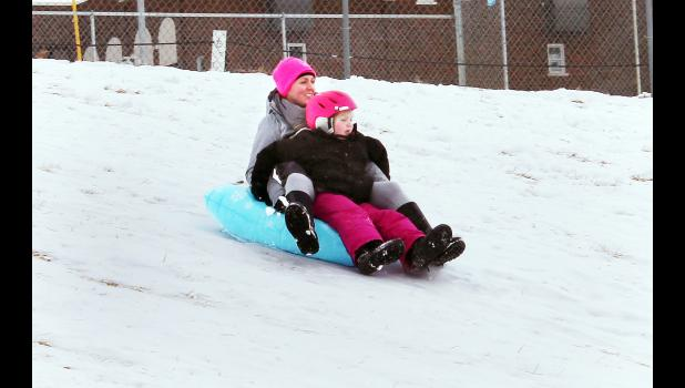 "Snow that fell on Jackson County over the weekend provided local thrill-seekers with an opportunity to take their sleds out to ""Pride Hill"" north of Holton High School and ride down the hill. On Monday, Alex Morrissey and daughter Mary were among those taking a ride down the hill on what had nearly become a sheet of ice. More snow fell on the area Tuesday night, and with students out of school on Wednesday as a result, more sledding opportunities were available. (Photo by Brian Sanders)"