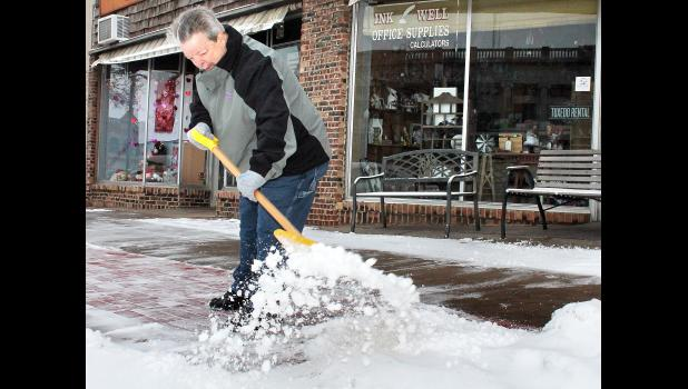 Friday morning saw Chris Koger of Koger Variety shoveling snow from the sidewalk in front of his business on the west side of Holton's Town Square after little more than an inch of snow fell on the area the night before. (Photo by Brian Sanders)