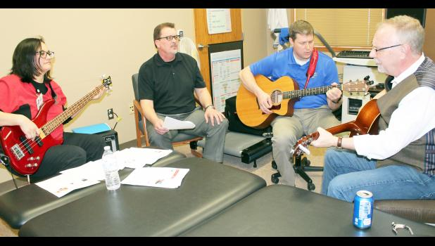 """From left to right, Michelle McClintock, Eric Bjelland, David Allen and Gary McKnight got together at Holton Family Health Clinic on Wednesday for a monthly jam session that McKnight said is """"good therapy."""" The quartet has been playing together for about a year, he said, mainly at the clinic. (Photo by Brian Sanders)"""