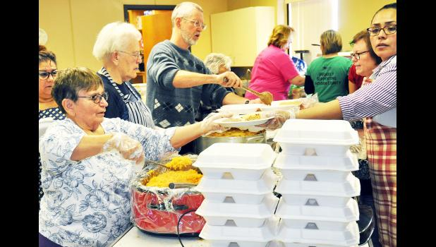 More than 400 meals were served on Friday at the Evangel United Methodist Church in Holton during the John Zibell Sr. Memorial Luncheon, which benefited the Zach Estrada family. Volunteers shown include, at left (front to back) Karen Gordon, Rosalie Lassiter and John Apel and at right (front to back) Gladis Gomez and Karen McCrory. (Photo by Ali Holcomb)