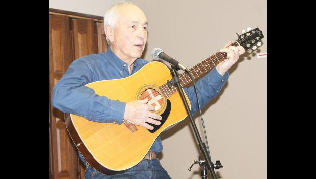 "Toward the end of his Thursday night presentation at the Jackson County Historical and Genealogical Society's Founders Day program, Kansas folklore expert and author Jim Hoy pulled out his guitar to illustrate the path that an old English folk song took to become the cowboy standard ""Streets Of Laredo."" The program marked 40 years since the historical society's inception. (Photo by Brian Sanders)"