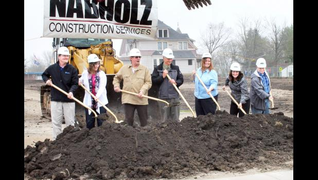 From left to right, Holton USD 336 Board of Education members Steve Bowser, Denise Sweet, Allen Arnold, Bob Phillips, Shelby Patch, Cindy Stavropoulos and Mike Ford turned ceremonial dirt on Wednesday afternoon at the construction site of the new Holton Elementary School, near the existing Colorado Elementary School. Shortly after the groundbreaking ceremony, the old Chandler house that stood behind them at the intersection of Fifth Street and Colorado Avenue was demolished. (Photo by Brian Sanders)