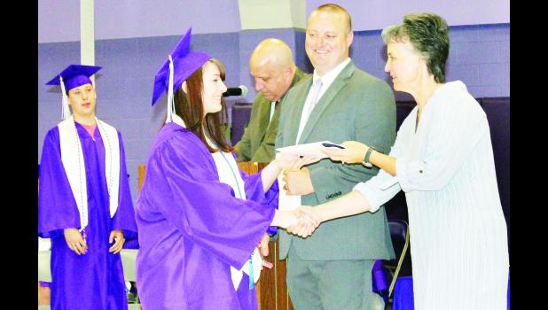Royal Valley Board of Education President Cindy Broxterman (right) presented a high school diploma to Chaley Lemmon on Sunday - one of 49 seniors from the Class of 2018 - as Superintendent Aaric Davis looked on. Also shown in the photo are RVHS Vice President John Martin in the background, who read the names of all the graduates, and senior Dawson Lyming (far left) who was next to receive his diploma. (Photo by Ali Holcomb)