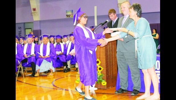 Royal Valley High School graduate Norma Wahwassuck (center) was one of the last seniors to receive their diploma from USD 337 Board of Education president Cindy Broxterman (right) and Superintendent Aaric Davis. RVHS Assistant Principal Travis Van Vleck is shown behind the podium announcing the names of all the graduates Sunday at the high school gym.