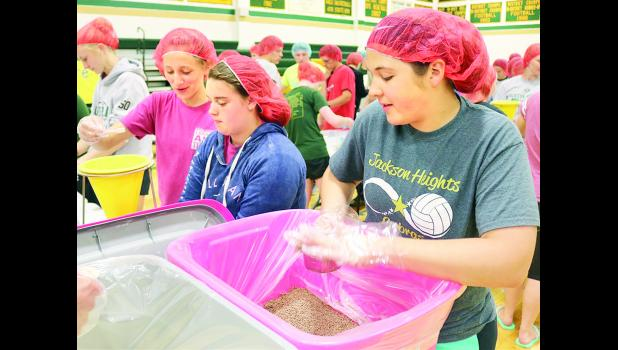JHHS students Erin Curtis (right) measured out ingredients for Jodi White (left) and Sadie Raborn to package as part of the school's participation in the Feeding Children Everywhere (FCE) program.