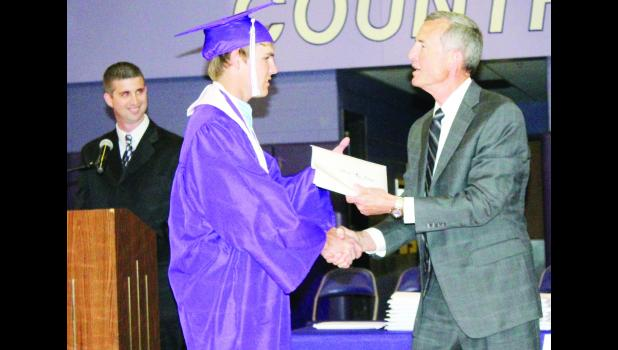 Royal Valley Superintendent John Rundle (right) is shown handing a diploma to graduating senior Nick Ehrhart (center) during Royal Valley High School's graduation on Sunday. Assistant High School Principal Travis Van Vleck is shown at left. This was Rundle's last graduation at Royal Valley as he is retiring at the end of the school year.