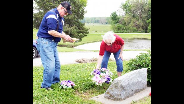 Fielden (left) and Marilyn Forgy, natives of Netawaka now living in Topeka, paid a visit to Holton Cemetery last Thursday to clean and decorate the gravesites of family members buried there. (Photo by Brian Sanders)