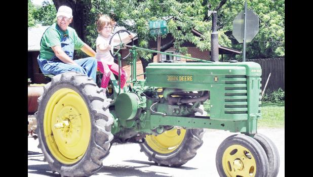 """Kenzie Liles, age 5, was probably the youngest entry in the Denison parade held Saturday during the """"Smoking' for the Park"""" event as she drove this tractor will assistance from her grandfather, Dan Goodman. (Photo by Ali Holcomb)"""