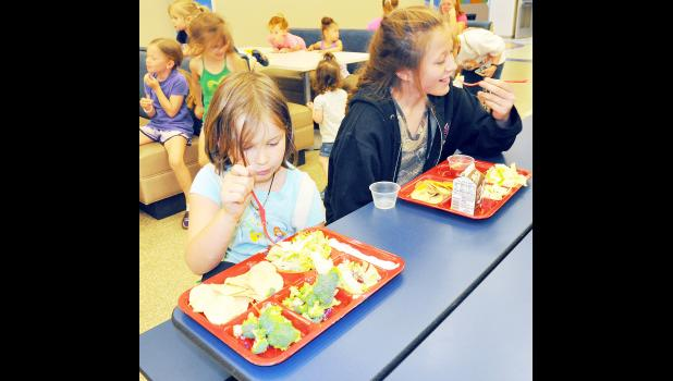 An average of 100 youth are taking advantage of the free lunches being served this summer at Holton Elementary School between 11 a.m. and noon each weekday, it was reported. Here, Elizabeth Boehm (left), 8, and Constance Kautz-Johansen, 12, are shown enjoying a recent lunch that included loaded nachos, fruit and vegetables. (Photo by Ali Holcomb)