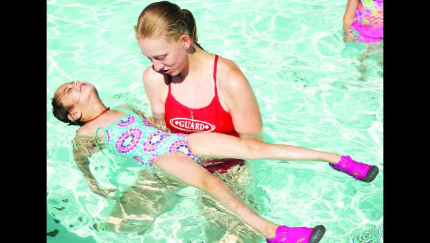"Holton Municipal Pool lifeguard Michaela Adcock (right) held Karis Owens, a student in the ""Tadpoles"" class for three- and four-year-olds at swimming lessons this week, afloat in the wading pool to teach Owens how to float on her back in the water during Tuesday morning's swim class. (Photo by Brian Sanders)"