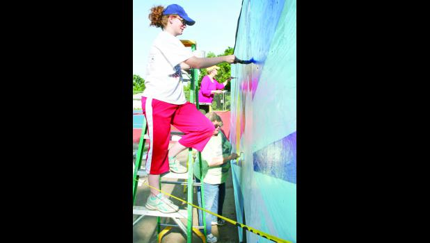 """From left, Katie Morris, Kathleen Cobb and Suzette McCord-Rogers could be seen on Thursday morning at Linscott Park, working on a new mural that decorates the """"practice wall"""" at the tennis court. (Photo by Brian Sanders)"""