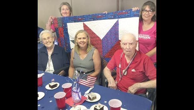 Local military veterans Dorothy Rogers (at left on front row) and Charles Scheidegger (at right on front row) were among 50 veterans honored at the second-annual Quilts of Valor event on Saturday. Organizers Julie Bahret (rear left) and Connie Morgan (rear right) helped organize the dinner and presentation. Also shown is Rogers' daughter, Jackie Sommers of Topeka. More than 300 dinners were served at the event. (Photo by David Powls)