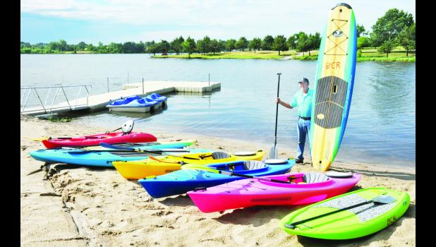 John Kennedy, Banner Creek Reservoir director, is shown above with several paddleboards and kayaks now available to rent at the reservoir. The equipment comes in both adult and youth sizes. In addition, two paddleboats (shown in the background) are available to rent.