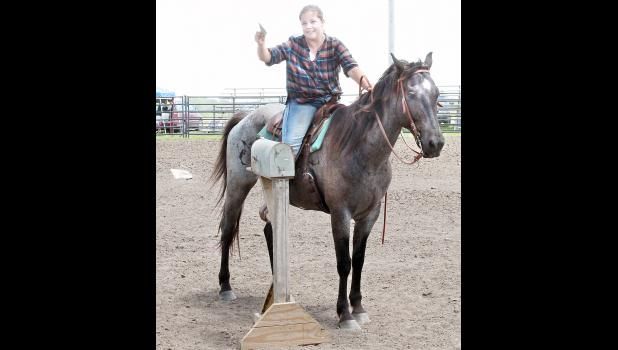 """Jarity Ribelin of the Hoyt Livewires 4-H Club pulled the """"mail"""" from the mailbox in the trail riding event at the recent Jackson County Fair horse show, although part of the """"mail"""" apparently decided to deliver itself elsewhere. (Photo by Brian Sanders)"""