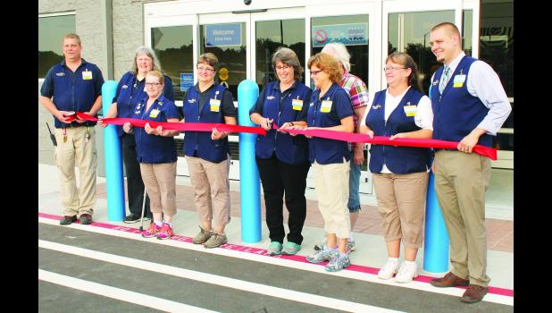 Holton saw the opening of a new Walmart store this morning with the ceremonial ribbon-cutting signaling the first day of business at the new, 24-hour store. Shown from left are Walmart employees Bob Basel, Michele Bloom, Dianna Beatty, Lisa Lehmkuhl, Lorrie Proctor, Cheryl Henry, Clara Lovvorn, Janet Corning and store manager Cale Worthington. At 70,000 square feet, the new store is nearly double the size of the old 38,000-square-foot store, Worthington said.
