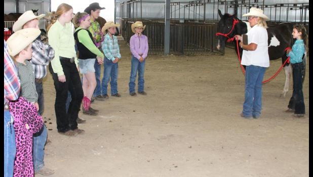 Just before Saturday's Jackson County Fair horse show came to a premature close due to rain, horse show judge Tossie Kirkham (second from right) met with younger showmanship contestants and gave them helpful hints on how to improve their performance. The rest of the horse show will be held starting at 8 a.m. Saturday, July 25 at the Northeast Kansas Heritage Complex, weather permitting. (Photo by Brian Sanders)