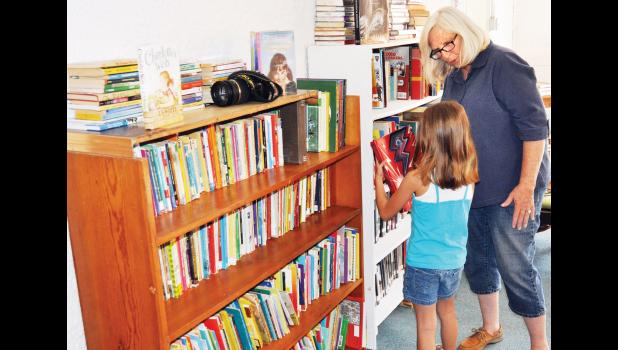 Vickie Wold (right), one of the organizers for the new free public library in Denison, helped Penny Hopkins, 7, select a book to check out during the library's grand opening on Friday. (Photo by Ali Holcomb)