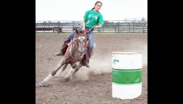 Sophia Mellenbruch of the Lucky Stars 4-H Club and her horse kicked up some dust as they rounded a barrel in the barrel race competition of the Jackson County 4-H Fair Horse Show, held Saturday at the Northeast Kansas Heritage Complex. (Photo by Brian Sanders)