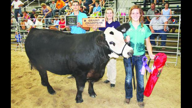 Thirteen-year-old Olivia Yingst (right) found herself having to deal with a somewhat unruly crossbred market steer at Tuesday's Jackson County Fair beef show at the Northeast Kansas Heritage Complex, but the struggle paid off in the end. Yingst's animal was named grand champion market steer of the show by judge Kayla Bodenhausen (center), after being named best heavyweight crossbred steer and best overall crossbred steer. Also shown in the photo above is 4-H Ambassador John Kennedy.
