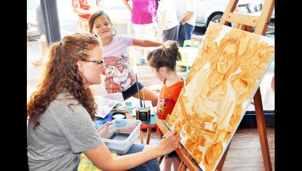 Jackson County Arts member Katie Morris (left) worked on a painting on the north side of the Holton Square during Saturday's Jackson County Art Walk as Nicole Amon (center), 6, and Becca Amon, 4, looked on. More than 50 artists were featured during Saturday's annual art walk that also included area musicians. (Photo by Ali Holcomb)