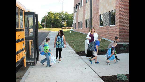 Holton Elementary School para Janelle Wareham (left) and teacher Becky Segenhagen welcomed school bus riders to the first day of school on Thursday, which was also the first day classes were held in the new school. (Photo by Brian Sanders)