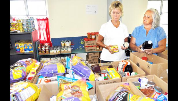 Jennifer Shaw (left) and Alecia O'Byrne are shown packing boxes of food at the Jackson County Ministerial Alliance New Hope Center Food Pantry, which is located in the basement of the First Christian Church in Holton. Shaw is stepping down as the director of the pantry at the end of the month, and O'Byrne will serve as her replacement. (Photo by Ali Holcomb)