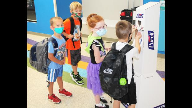 The 2020-21 school year in Holton began on Monday with students taking precautions to halt the possible spread of COVID-19 before entering the Holton Elementary School building. Here, students Parker Harris (left), Michael Anderson (second from left), Michelle George (second from right) and another student entering the building stopped to apply some hand sanitizer. (Photo by Brian Sanders)