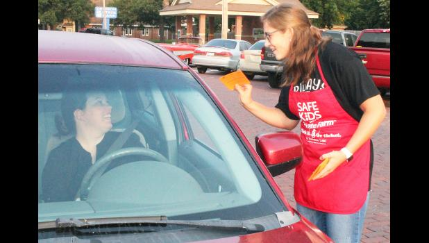 """It pays to buckle up for safety — that's what motorists driving through the intersection of Fifth Street and New York Avenue were reminded of recently via the """"Bucks For Buckles"""" campaign sponsored by Safe Kids Kansas, State Farm Insurance and the Kansas Department of Transportation. Here, Holton High School senior Paige Crouch (at right) gave motorist Vanessa Ogden some information on the importance of buckling up. (Photo by Brian Sanders)"""