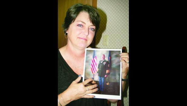 Lisa Deghand is shown above holding a picture of her late husband, Sergeant First Class Bernard Lee Deghand, who was killed in Afghanistan.