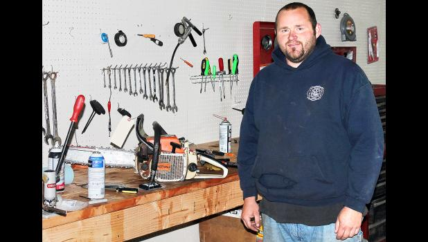After several years as the small engine repairman at Holton Farm and Home, Sam Schumaker has opened his own business, Sam's Equipment Sales and Service, north of Holton, where he continues to provide expert service on small engines, such as the chainsaw he was working on Friday morning. (Photo by Brian Sanders)