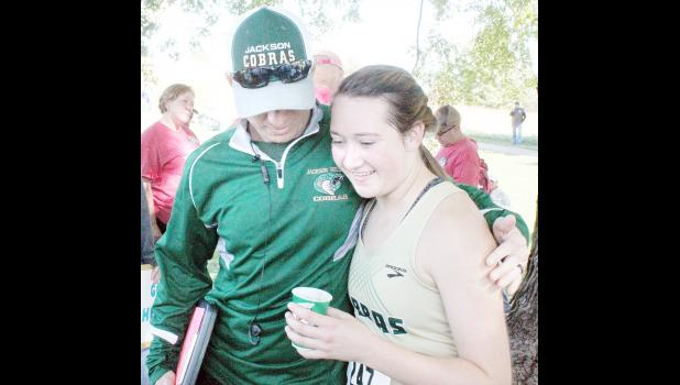 Jackson Heights High School senior Faith Little (right) got a hug from head cross-country coach Brad Alley after Little completed in her fourth and final state high school cross-country race on Saturday at Wamego. Little placed in the top 30, while her younger brother, freshman Daniel Little, placed ninth in the boys' race. (Photo by Brian Sanders)