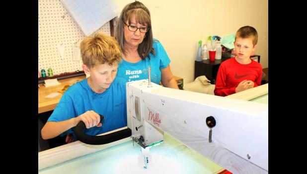 "Jeffrey Warner (left), a sixth-grader at Holton Middle School, used a long-arm quilting machine to ""write"" his name on a quilt with assistance from Quilting on the Square's Connie Morgan (center) on Friday afternoon while Holton Elementary School fifth-grader Carter Colberg looked on. (Photo by Brian Sanders)"