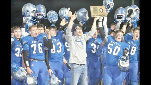 Holton's football players celebrate another playoff win by raising the sub-state championship trophy after Friday's thrilling 23-22 victory over Columbus. With the win, the Wildcats will advance to the 4A-DII state title game to face Holcomb at 1 p.m. on Saturday in Salina. (Photo by Kelly Breckunitch)