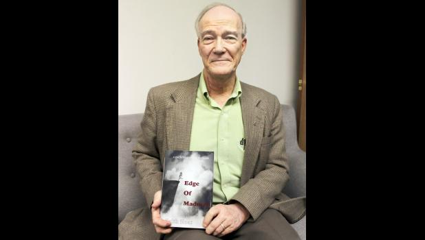 "Holton resident Keith Hoar is shown with his first novel, ""Edge Of Madness,"" which has drawn comparison to the work of Tom Clancy. (Photo by Brian Sanders)"