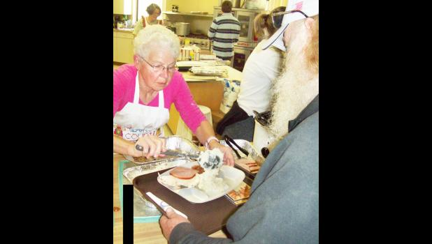Jean Lierz of Holton dished out mashed potatoes for hungry diners at the annual Community Thanksgiving Dinner, held Thursday at the EUM Family Life Center. Dinner organizer Freda Galer said a total of 375 dinners were served at Thursday's event. (Photo by Allen Bowser)