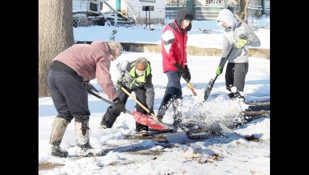 """Members of Holton High School's wrestling team — from left, Drew Morris, Cale Hein, Braden Peven and Conner Gilliland — shoveled snow off driveways and sidewalks at homes near HHS on Tuesday afternoon. Head Wrestling Coach Cullen Jackson said team members needed to """"burn off some nervous energy"""" after their Thanksgiving break was extended by two days due to Sunday's blizzard. Students in all Jackson County schools got Monday and Tuesday off due to the snowstorm. (Photo by Brian Sanders)"""