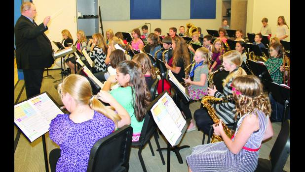 Holton school band director Jayme Malsom (at left) led the fifth-grade band at Holton Elementary School through the songs that made up not only their first concert, but also the first concert to be held at the new school, on Tuesday evening. The sixth-grade band also performed during Tuesday's concert.
