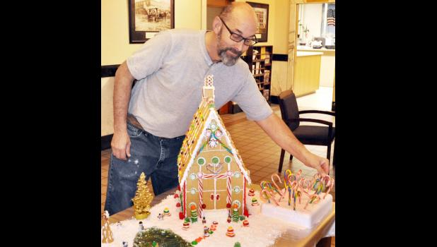 Chad Phillips, Jackson County Courthouse custodian, is shown above adjusting a gingerbread house display on the second floor of the Courthouse recently. Phillips constructed the display, as well as a large Christmas tree made of pine cones on the first floor of the building, for the Christmas season. (Photo by Ali Holcomb)