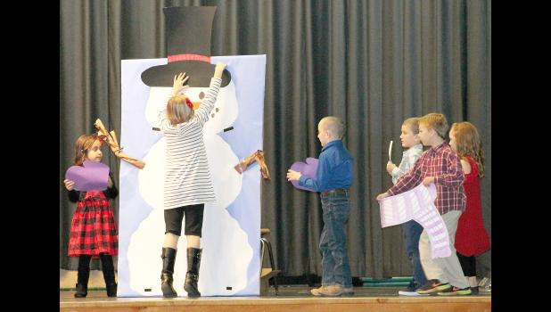 "During the song ""A Hat For My Snowman,"" several Royal Valley Elementary School kindergarten students decorated this paper snowman for winter. The song, along with three others, were a part of the student's winter holiday program performed on Monday at the school. (Photo by Ali Holcomb)"